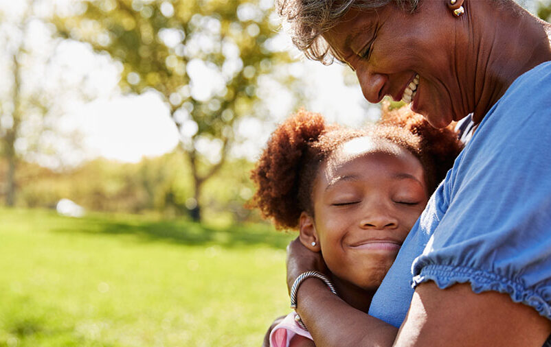 mulher abraçando a neta em um jardim represente os avós pagam a pensão alimentícia dos netos